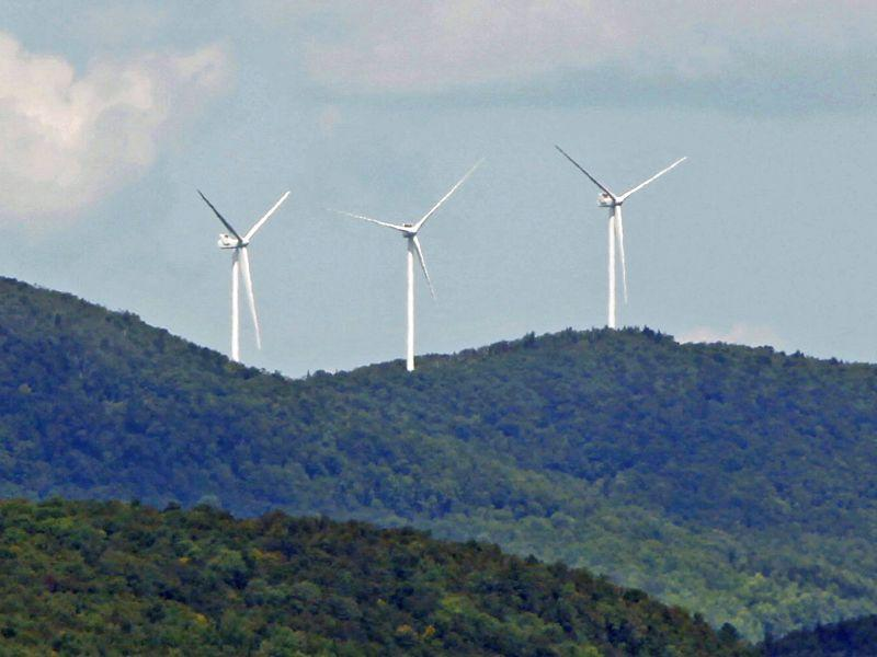 A file photo shows wind turbines along a mountaintop in Lowell. We're talking about the reliability challenges faced by the electrical grid as renewables boom.