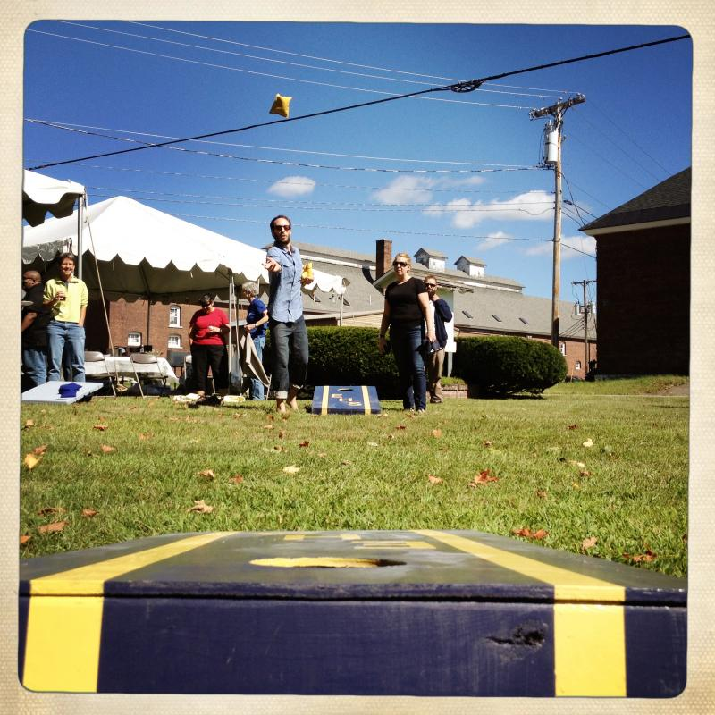 Matt Parrilla tosses a bean bag in a competitive game of corn hole.