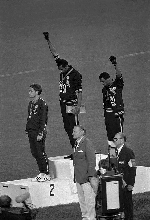 Extending gloved hands skyward, U.S. athletes Tommie Smith, center, and John Carlos stare downward after Smith received the gold and Carlos the bronze for the 200 meter run at the Summer Olympic in Mexico City on Oct. 16, 1968.