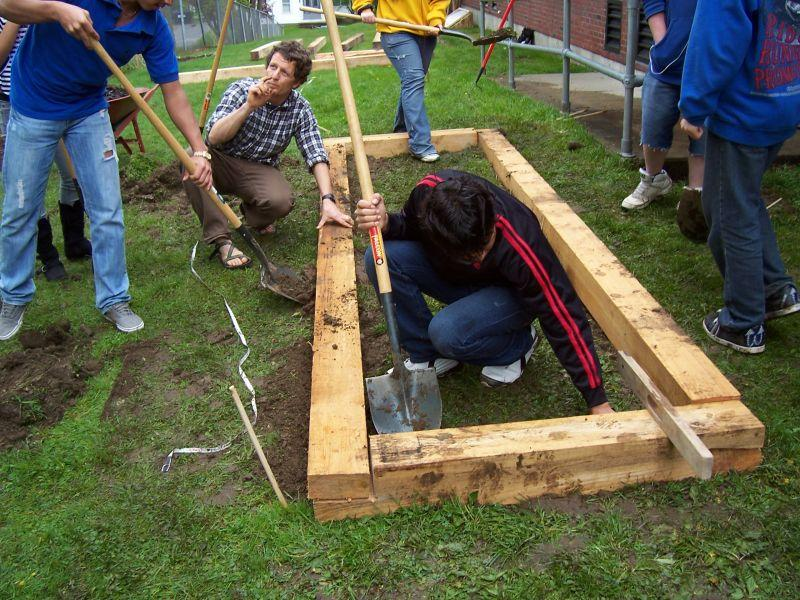 Luke Foley working with students to build raised beds in the school garden