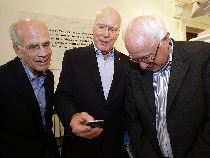 Sen. Patrick Leahy, center, shares photos of his grandchildren on his smart phone with Sen. Bernie Sanders, right, and Rep. Peter Welch, in July 2012, in Montpelier.