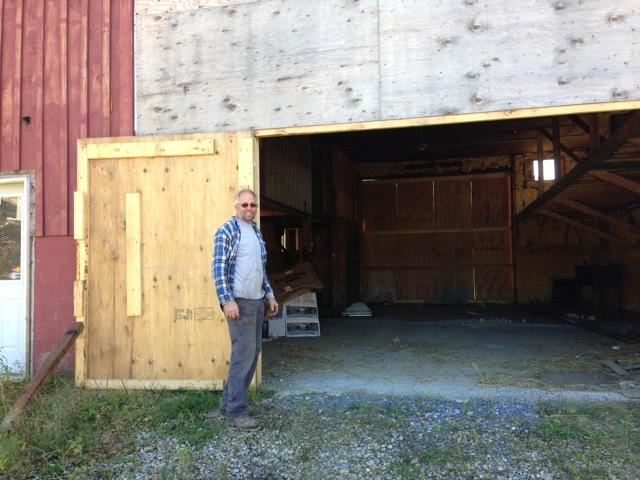Frank Sprague, welder and stone mason, standing in front of his flood-damaged barn  in Wilmington, VT. The town is buying it with FEMA funds and demolishing it. Sprague would like to see a trail built here.