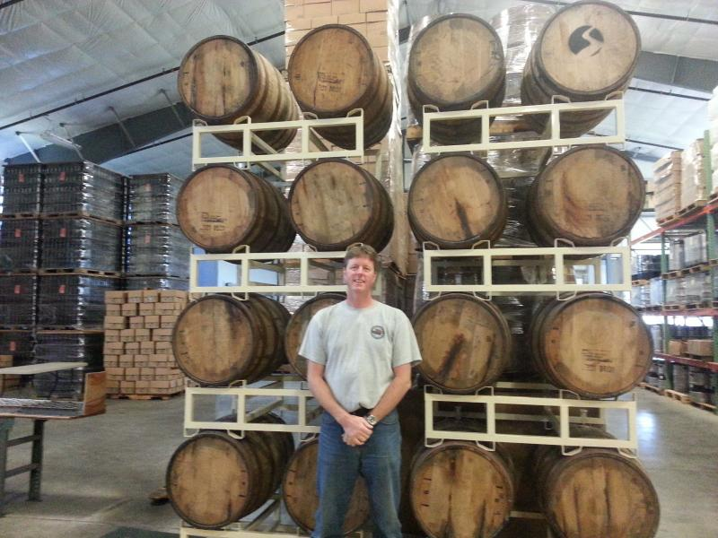 Rock Art Brewery's Matt Nadeau stands in front of oak barrels filled with Russian imperial stout. The product is still waiting on federal approval.