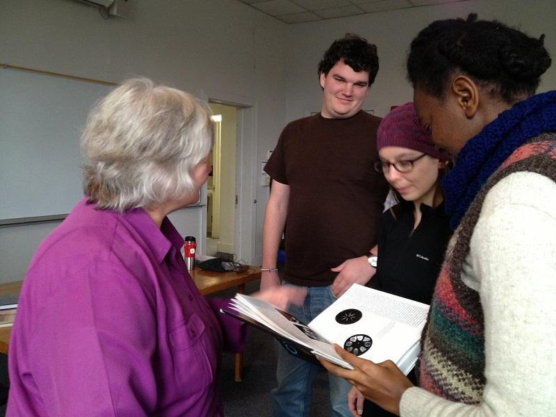 Harpist Linda Schneck talks with Johnson State College students Maxwell McKenzie, Antonia Miranda, and Janet Munyiri after lecture about the healing properties of music.