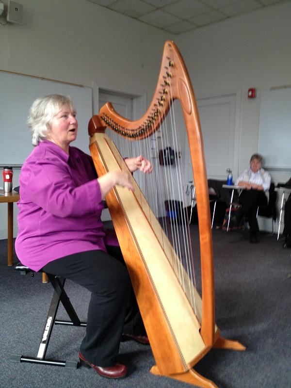 Linda Schneck plays harp for wellness students at Johnson State College.