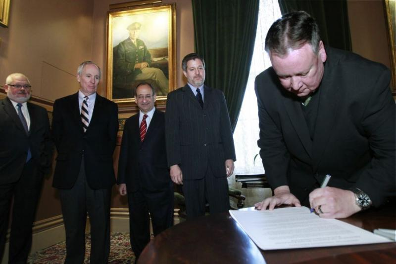 Vermont Technical College President Phil Conroy, right, signs a memorandum of understanding to create the Vermont Higher Education Food Systems Consortium