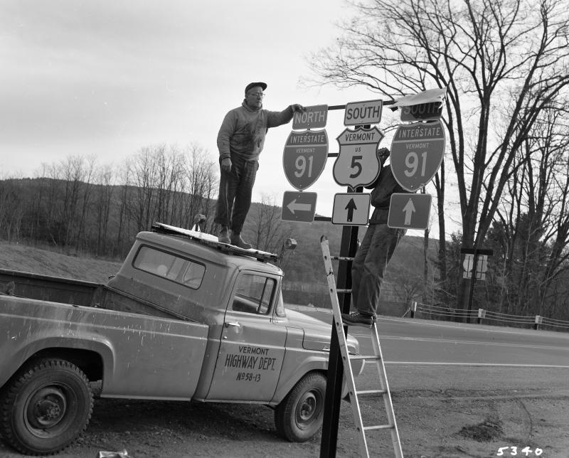 Employees of the Vermont Highway Department install road signs at an opening ceremony for I-91 in Putney.