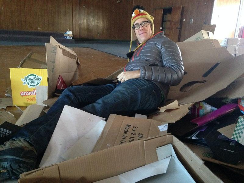 Developer Matt Bucy reclines on a pile of trash in the building he wants to convert into apartments and offices in White River Junction.