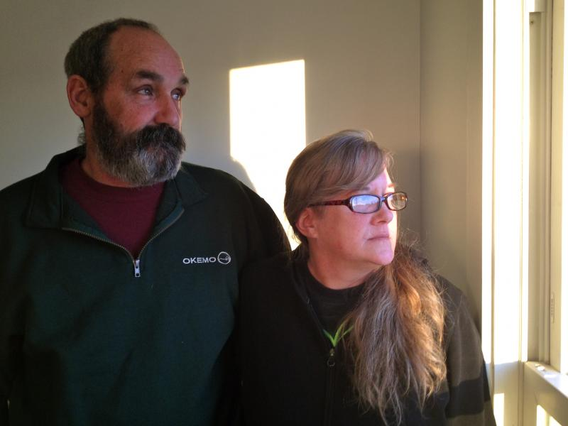Neil and Patricia Whitney stand in the empty kitchen of their new apartment looking at their home across the street.  The couple says they had to flee their home last April and leave all their belongings after a botched treatment for bedbugs.