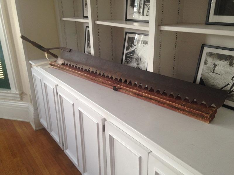 An ice saw rests under photos collected by the St. Johnsbury History and Heritage Center.