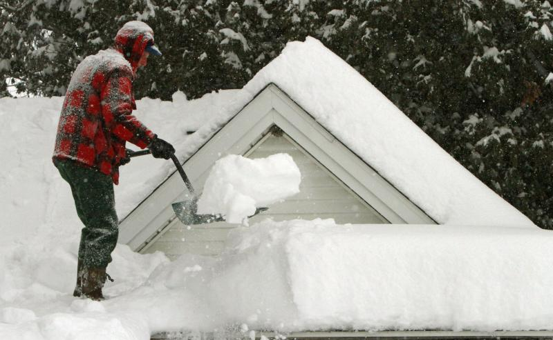 In this Feb. 2, 2011 file photo, Harry Eastman shovels the snow off his garage roof in Barre, Vt. Doctors across the battered Northeast are seeing a spike in strained muscles from shoveling snow, and broken bones from slick stairs and sidewalks.