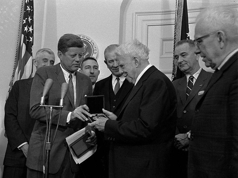 Poet Robert Frost looks at the congressional medal after it was presented to him March 26, 1962, by President John F. Kennedy at a White House ceremony. The award was for his contribution to American letters.
