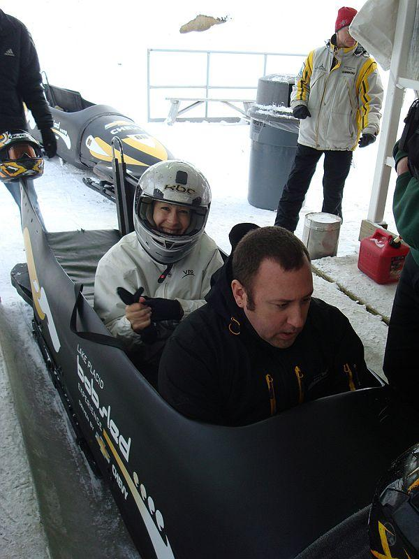 VPR's Patti Daniels settles into bobsled behind a professional driver. (He wore a helmet too, no worries.)