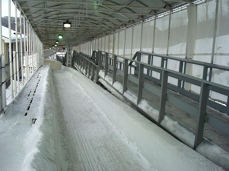 Bobsled tracks are required to finish on an uphill slope. This viewpoint looks from the finish line down the track where sleds will appear in the final seconds of their runs.