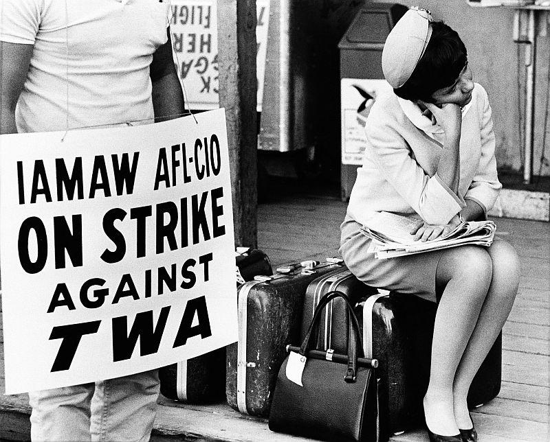 Judy Taylor, a TWA flight attendant based in New York, sums up the sentiments of thousands of stranded travelers as she sits on her baggage at Boston's Logan Airport, July 8, 1966, after the start of the nationwide strike of five major airlines.