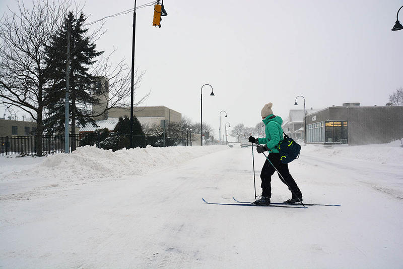 Tori Carton, an employee of Hotel Vermont, skis across Pearl Street on her way to work Thursday.