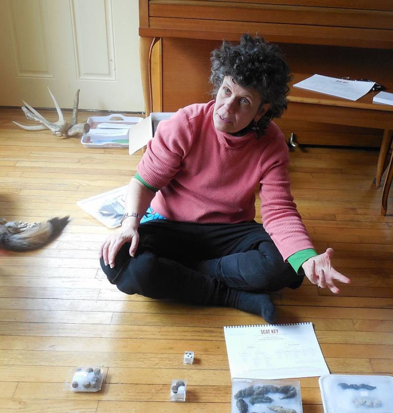 Lynn Levine refers to some commercially-packaged scat samples during a workshop in her living room.