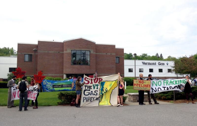 Protestors stood in front of the Vermont Gas building holding signs expressing opposition to the company's pipeline plans.