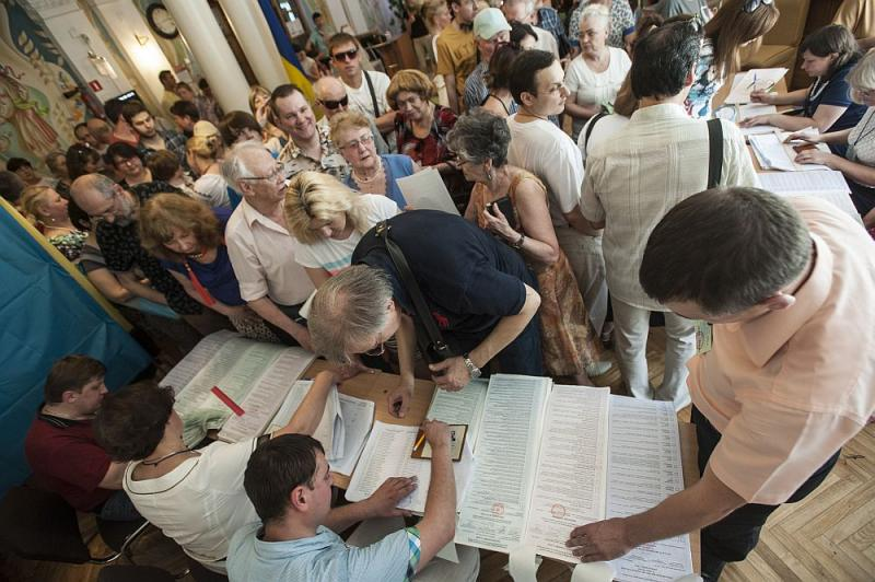 Ukrainians stand in line to receive their ballots at a polling station during presidential and mayoral elections in Kyiv, Ukraine, Sunday, May 25, 2014.