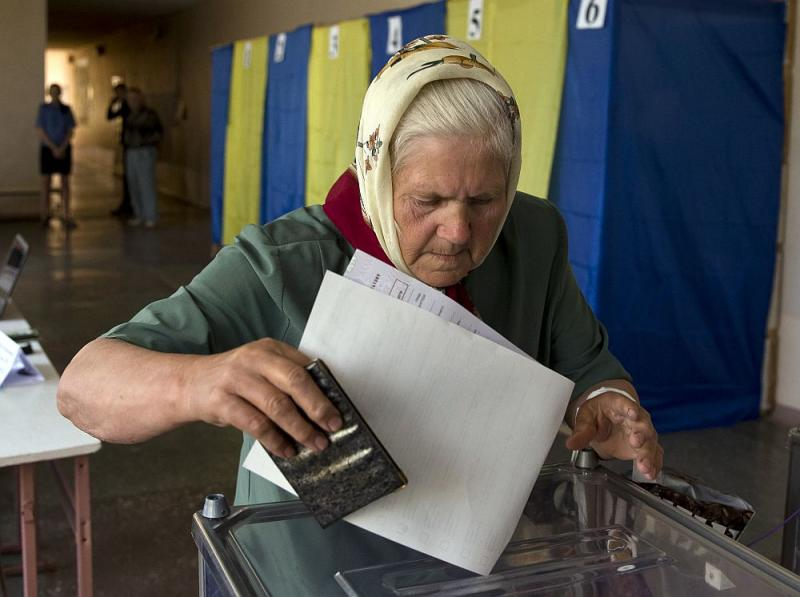 An elderly woman casts her vote in the presidential election in the eastern town of Krasnoarmeisk, Ukraine, Sunday, May 25, 2014.