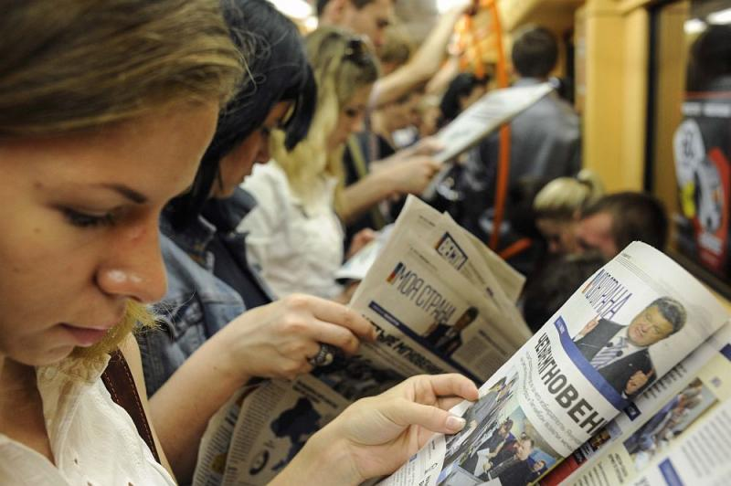 Ukrainians read newspapers at a metro station, in Kyiv, Ukraine, Monday, May 26, 2014. Early returns on Monday suggested candy tycoon Petro Poroshenko was ahead in the first round of balloting of the Ukraine presidential election.