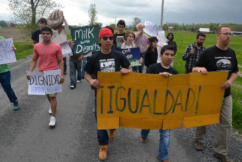 Migrant workers and activists protest poor working conditions at a Ferrisburgh farm on Friday.