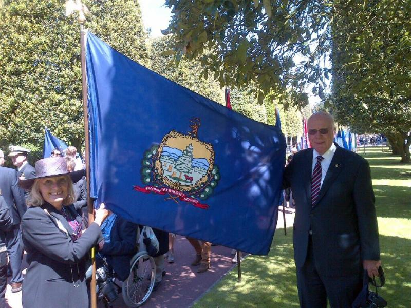 Marcelle and Patrick Leahy stand with Vermont's state flag at the D-Day ceremony entrance at the U.S. cemetery in Normandy.