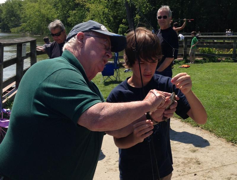 Instructor Karl Hubbard gives Caden Relyea, 11, tips on identifying his most recent catch.