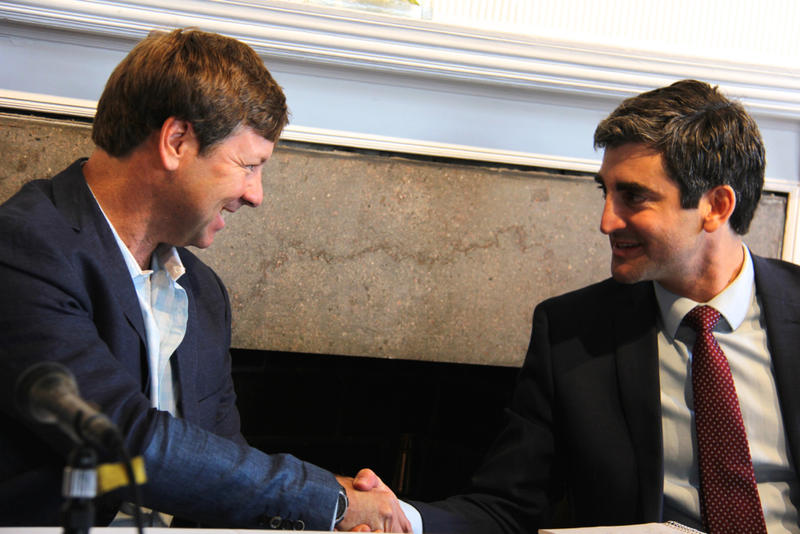 Trey Pecor (left) shook hands with Mayor Miro Weinberger after signing a deal to help finance the settlement between Burlington and Citibank.