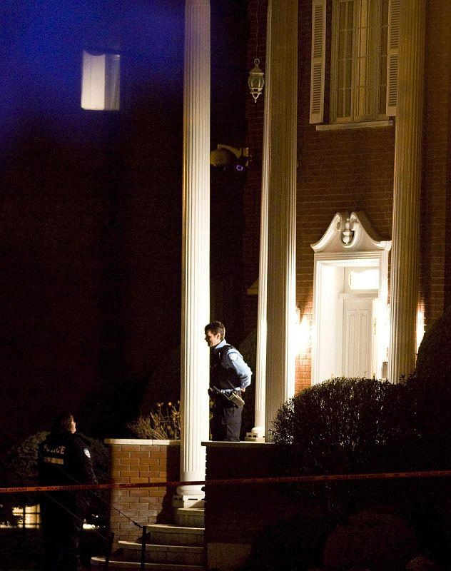 Police gather outside the house of reputed mafia boss Nicolo Rizzuto Sr., who was reportedly gunned down in his home in Montreal in November 2010.