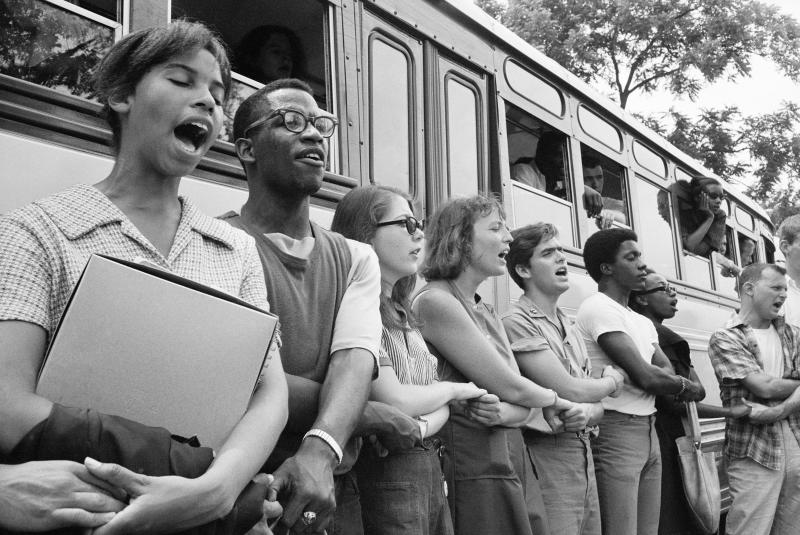 Student civil rights activists join hands and sing as they prepare to leave Ohio to register black voters in Mississippi in 1964.