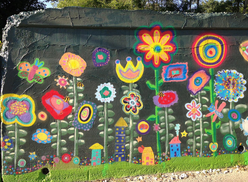 The completed mural includes flowers, bugs and fairy houses all inspired by children's artwork.