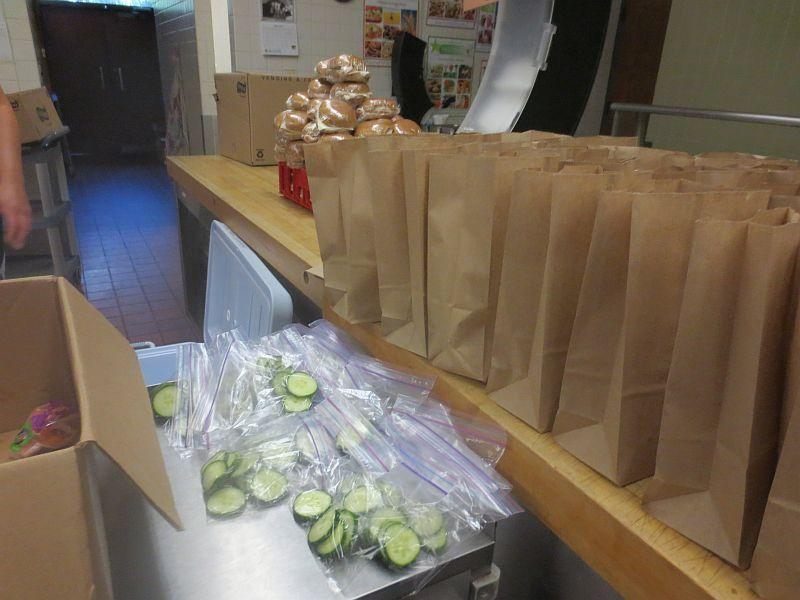 Paper bag lunches lined up on a table and plastic bags of cucumber slices.