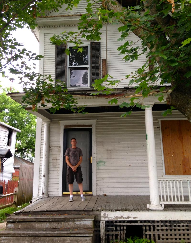 Kelly Greene stands on the front porch of the home he recently purchased and is renovating in northwest Rutland.