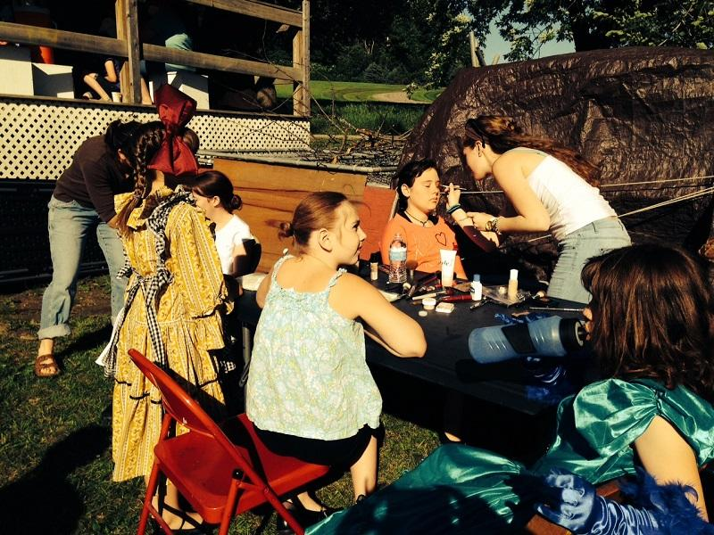 Adults help young actors apply makeup outside Vermont Children's Theater.