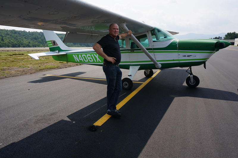 Project Consultant Mark Greenberg poses by a plane on the new blacktop.