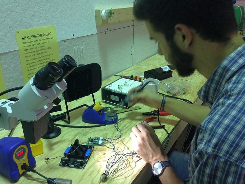 Asa Mease of Williston solders wires at a workbench at Generator. A student of biology and art, making an amplifier for his dorm room is Mease's first foray into electronics.