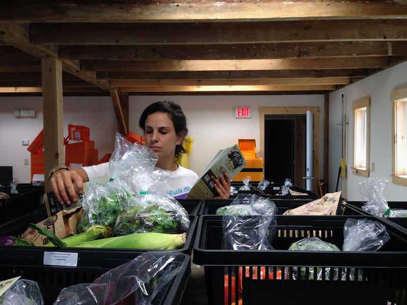 Sam Rothberg of the food hub finishes preparing the UVM delivery.