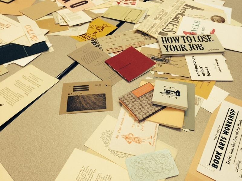 Printed materials created by letterpress cover a table at a workshop given by Dartmouth College.
