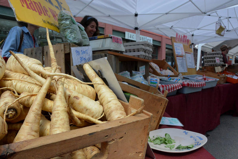 A box of parsnips from Maple Wind Farm awaits shoppers at the Burlington Farmers Market in May. Over the past five years, local food systems have grown at a rate of 3 percent, while Vermont's economy as a whole has only grown at a rate of 1 percent.