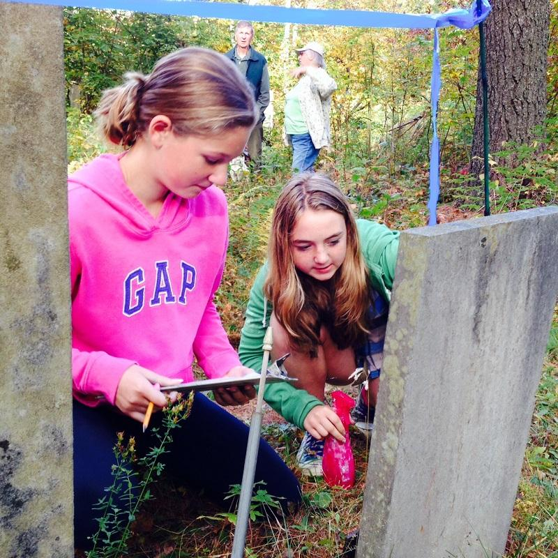 Nicole Harrington and Lowry Newswanger, seventh graders at The Sharon Academy, examine a grave as part of a social studies project at the middle school.