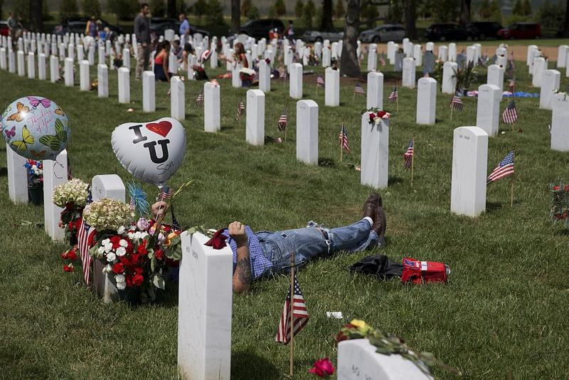 Jason Feimster, of Mocksville, N.C., lies by the grave of his friend, Marine Cpl. Carlos Melendez in Section 60.