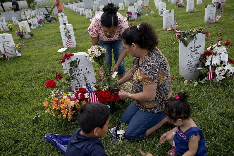 Gladys Mena, of Springfield, Va., center, places flowers on the grave of her nephew, Army Corporal Andy Anderson in Section 60.