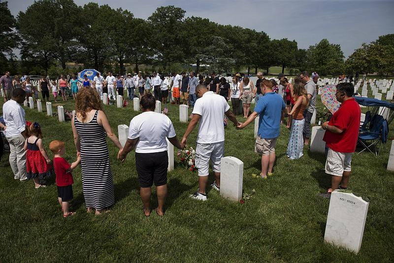 A spontaneous prayer circle forms as people visit Section 60, where many of the soldiers who died in Iraq and Afghanistan are buried, on Memorial Day in 2014.