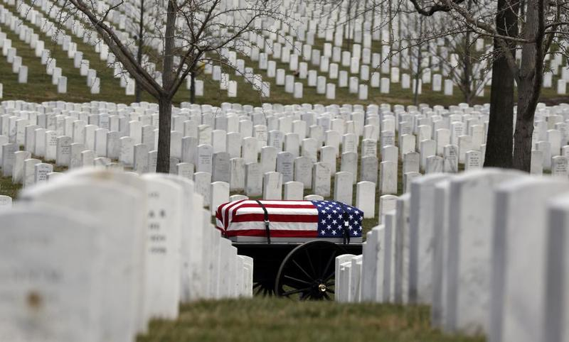 A caisson holding the flag covered casket is taken to a burial site during a service at Arlington National Cemetery.