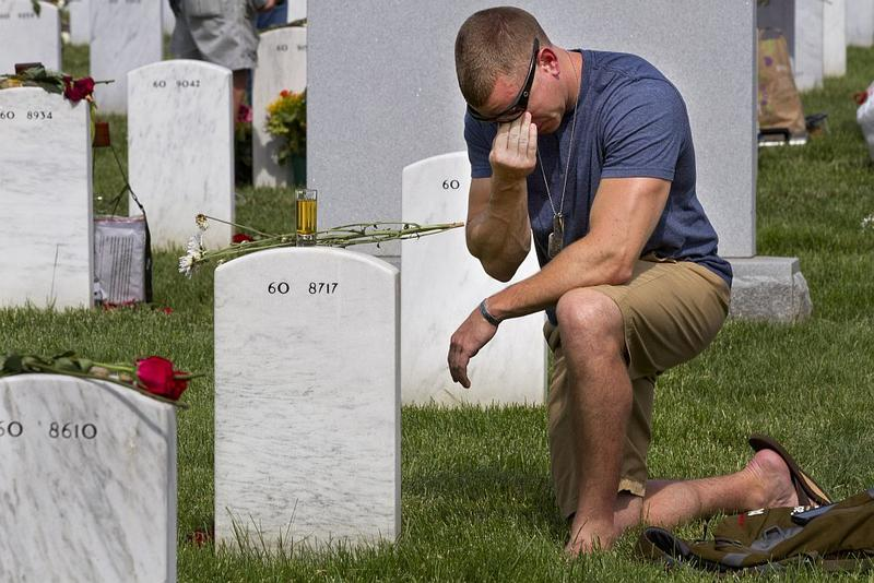Former Army Sgt. Anthony Brown, 31, of Arlington, Va., wipes away tears as he visits the grave of his best friend, Army Sgt. Scott Kirkpatrick, on Memorial Day 2014.