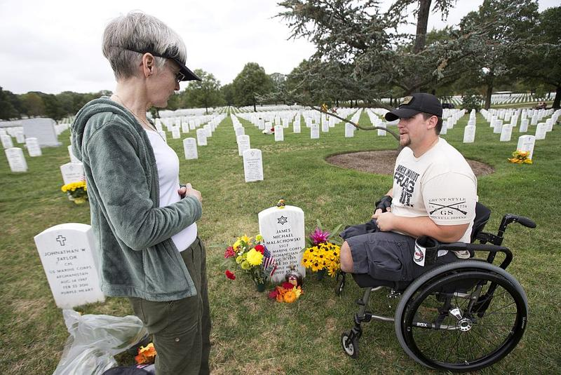 Alison Malachowski, left, talks to Michael Frazer, who served in Afghanistan with the U.S. Marine Corps together with her son Marines Staff Sgt. James M. Malachowski. She became friends with author Robert Poole as he researched his book about Section 60.