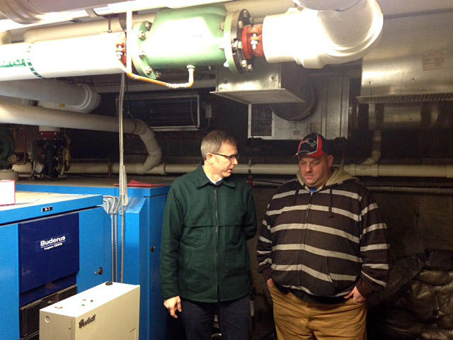 Logan Brown of Commons Energy, left, and Scott Walder, facilities manager at Union Square apartments in Windsor, discuss the replacement of the two oil-fired boilers in the basement of the building.