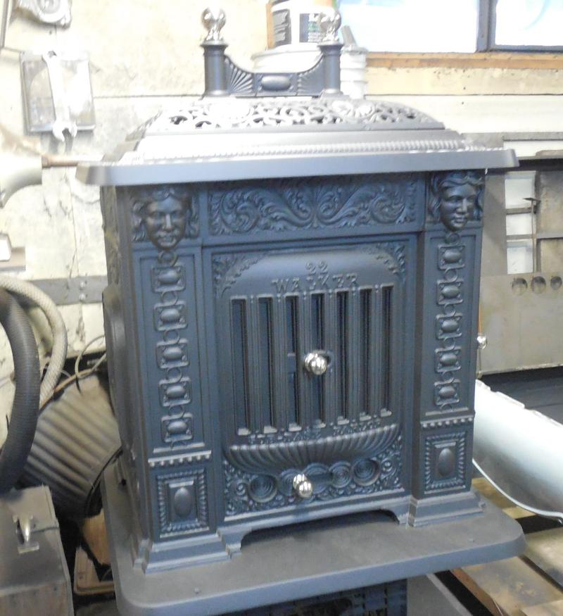 This rare Walker stove features faces stamped in the cast, front and back.
