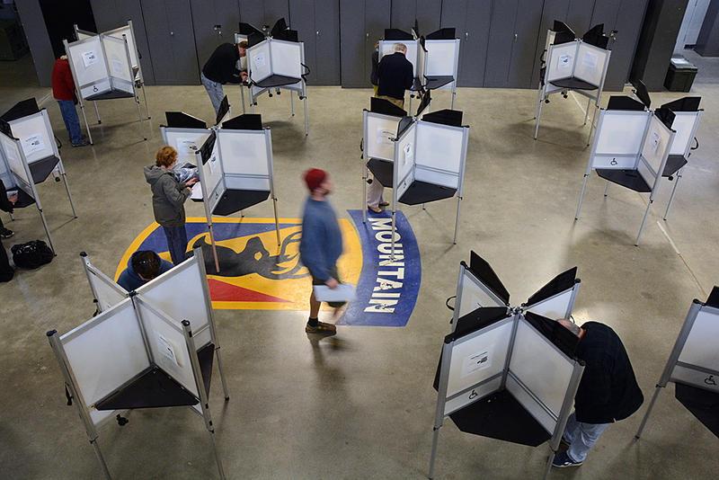 Voters cast their ballots at the Williston Armory on Tuesday. Vermont law does not expressly forbid ballot box selfies.